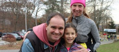 Image of family bundled up and smiling; Clearpool's fall setting in the background.