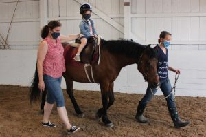 Preschooler rides pony while one adult leads the horse and another adult supports the student.