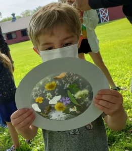 Preschooler holds a project made up of a cardboard circle, a translucent contact paper center with flowers and leaves placed on it.